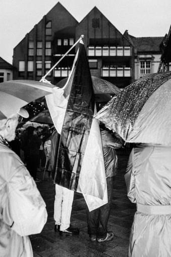 Menschen mit Deutschlandfahnen im Regen