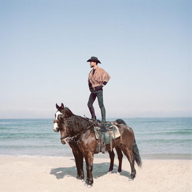 Ein Mann steht auf einem Pferd am Meer