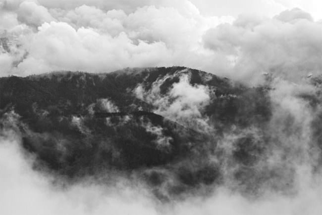 Bewaldete Berghänge in tiefhängenden Wolkenfetzen