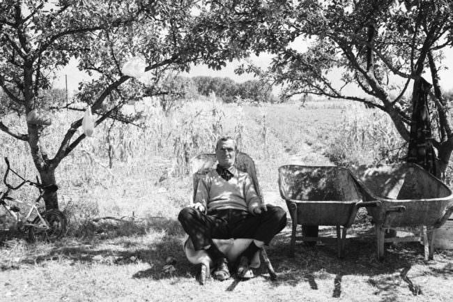 Ein Mann sitzt auf einer Schubkarre