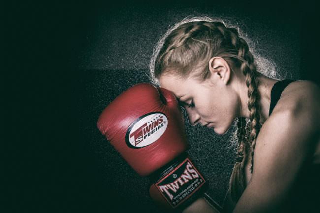 Junge Frau mit Zöpfen und Boxhandschuh.