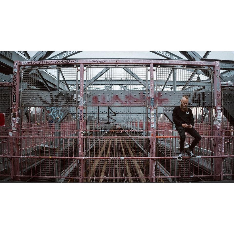 Ein Mann sitzt auf dem Geländer einer Zugbrücke und blickt auf sein Telefon.