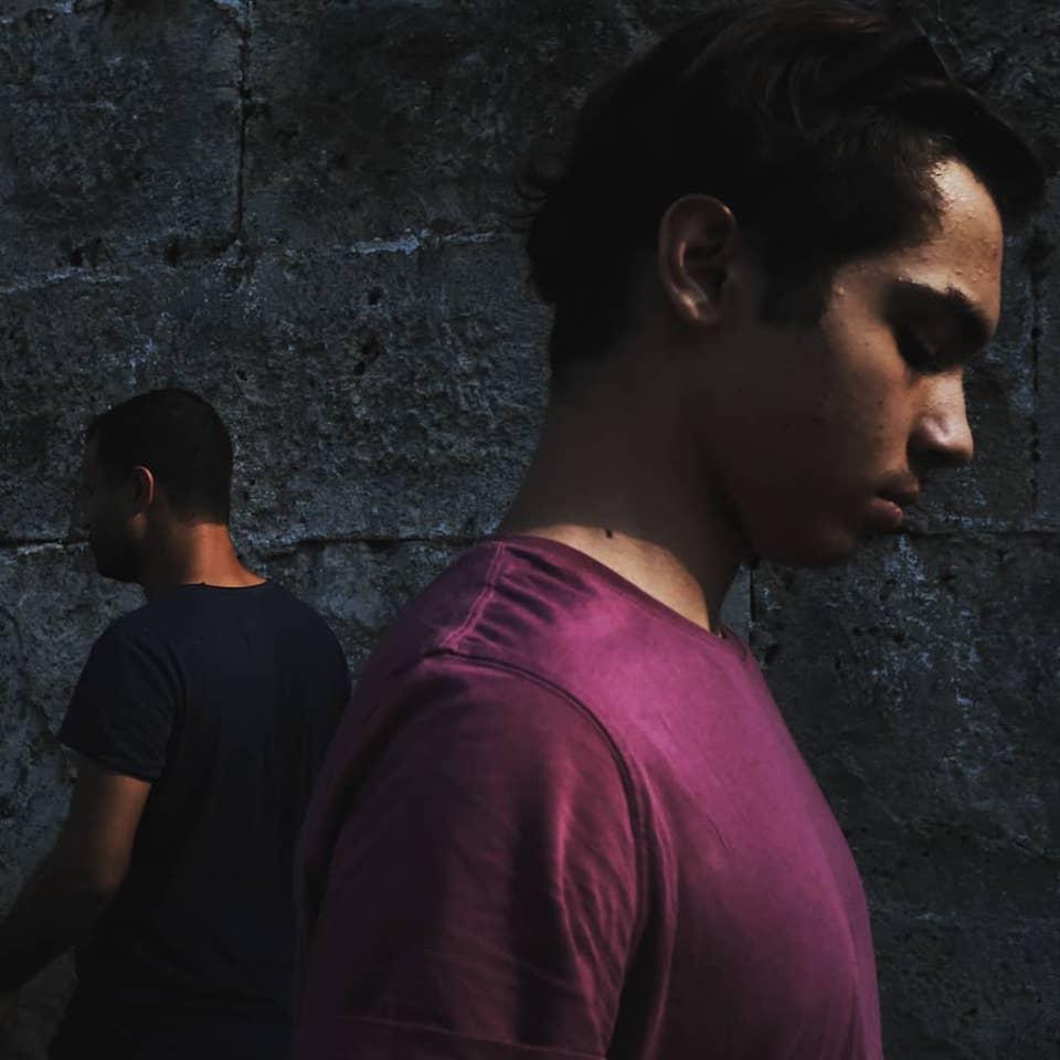 Zwei Männer laufen aneinander vorbei. Der eine ist im Bildvordergrund, der andere im -hintergrund.