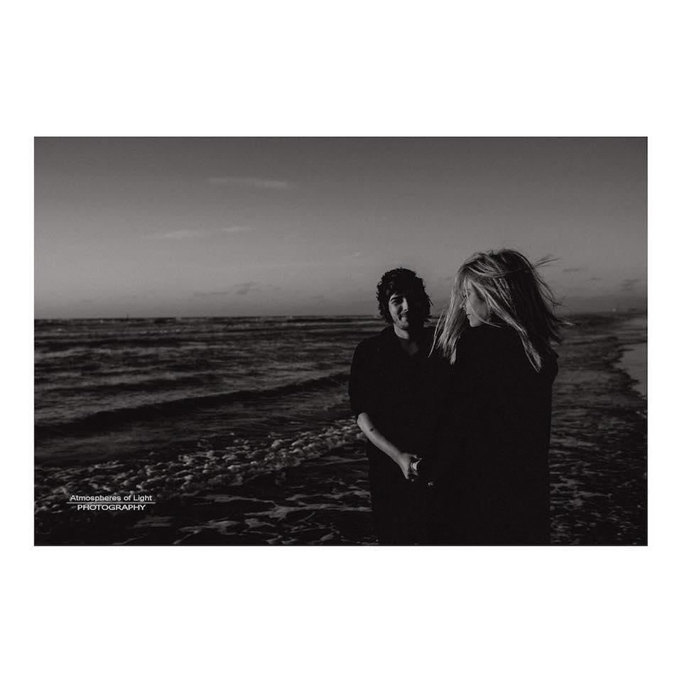 Zwei Personen stehen an einem Strand.