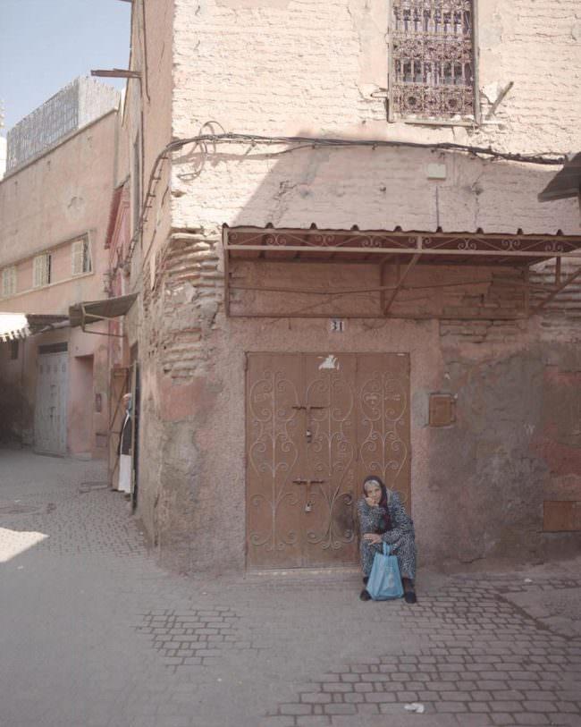 Eine ältere weibliche Person sitzt vor einem Haus aus Backsteinen.