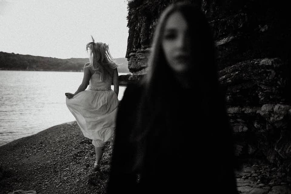 Zwei Frauen von denen einen schwarz und eine weiß trägt. Eine der Frauen blickt in die Kamera die andere bewegt sich im Hintergrund davon weg.