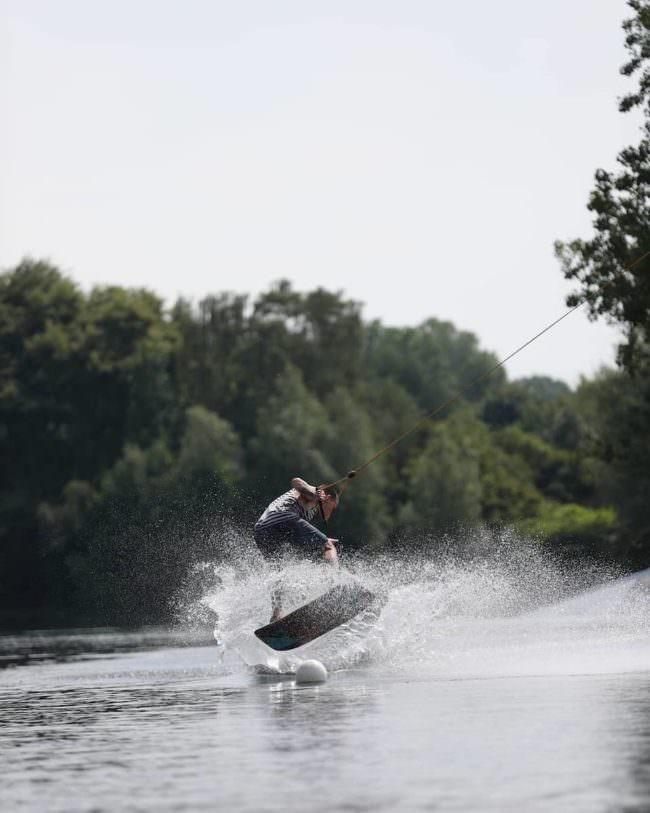 Eine Person auf einem Surfboard auf einem See.