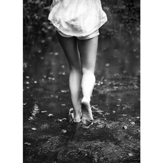 Frau läuft ohne Schuhe am Strand