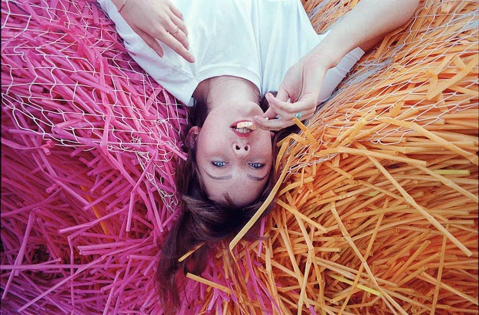 Eine weibliche Person liegt auf orangenen und pinken Strohhalmen.