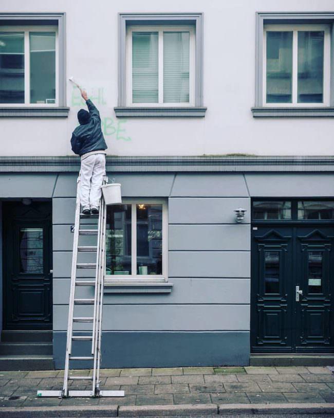 Eine Person steht auf einer Leiter und streicht eine Hausfassade.
