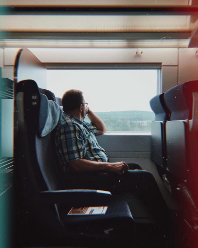 Eine männliche Person sitzt in einem Zug und blickt aus dem Fenster.