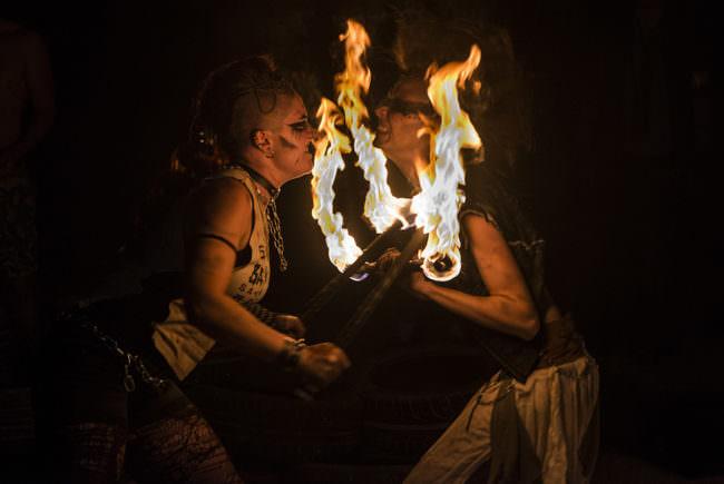 Zwei Personen im Dunklen mit Flammen an Stäben.