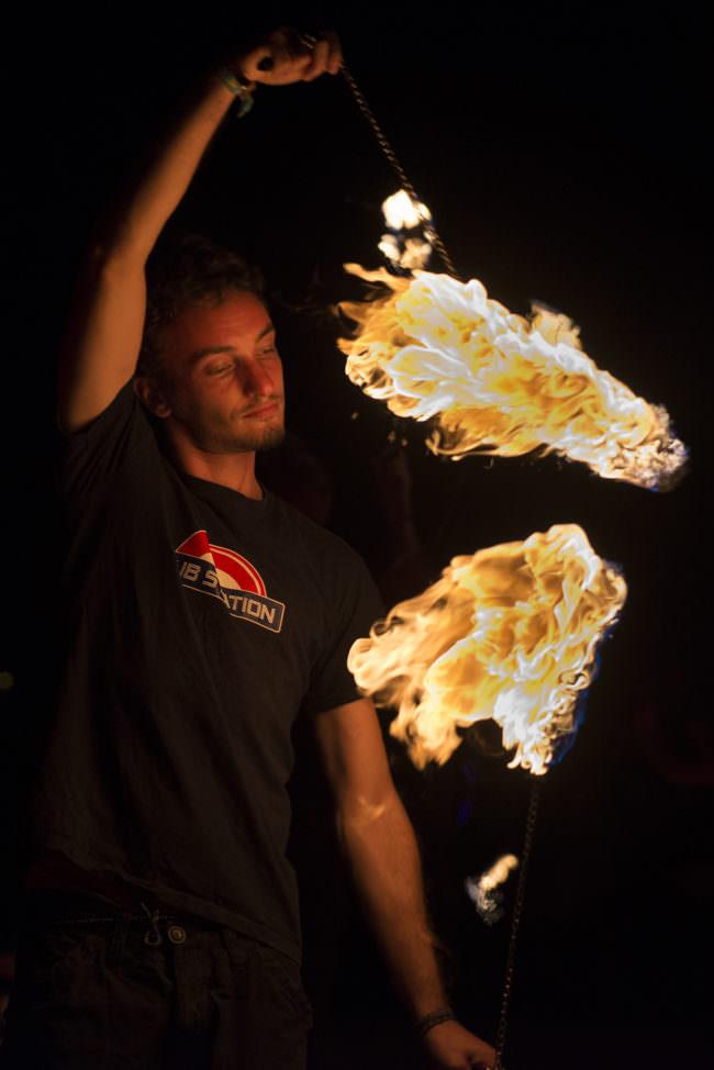 Ein junger Mann mit Flammen an Schnüren.