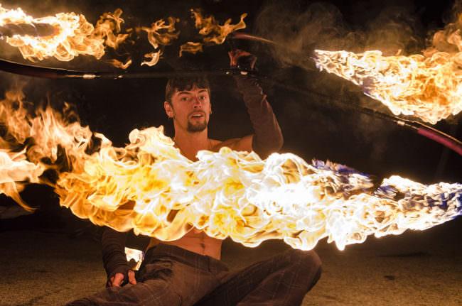 Mann im Dunklen mit Flammenkreis um sich.