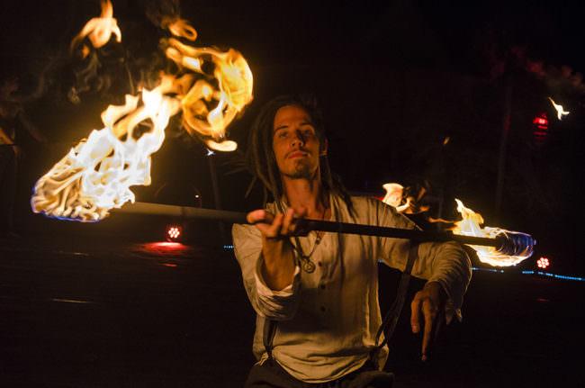 Junger Mann und Stab mit brennenden Enden.