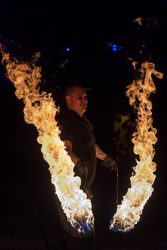 Mann im Dunkeln mit zwei Feuerfontänen neben sich.