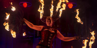 Eine Frau in Kostüm mit brennenden Fächern.