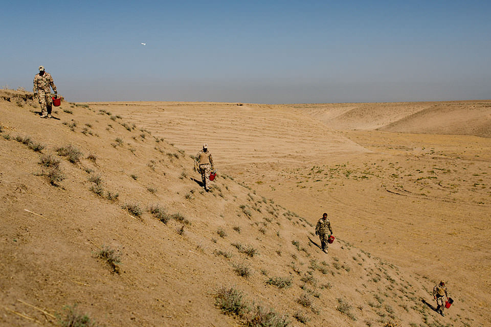Soldaten laufen einen Berghang entlang