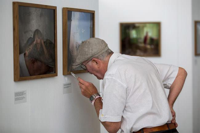 Ein Mann liest mit einer Lupe den Beschreibungstext eines Bildes