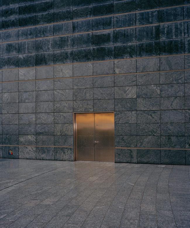Goldene Tür in einer Steinwand.