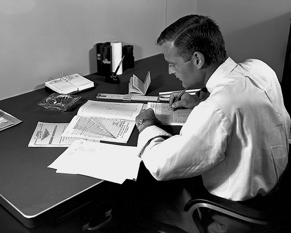 Mann an einem Tisch mit vielen Papieren.