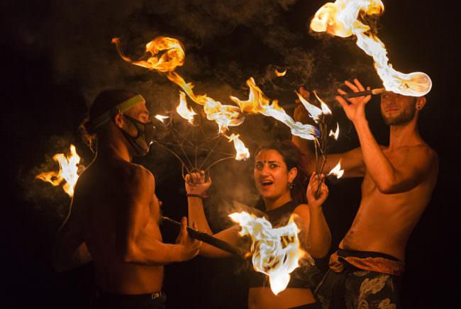 Drei Personen im Dunklen mit Flammen an Stäben.