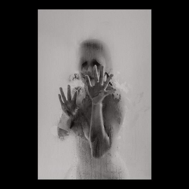 Nackte Frau vor beschlagener Glasscheibe.