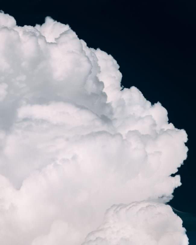 Weiße Wolkenberge vor schwarzem Himmel.