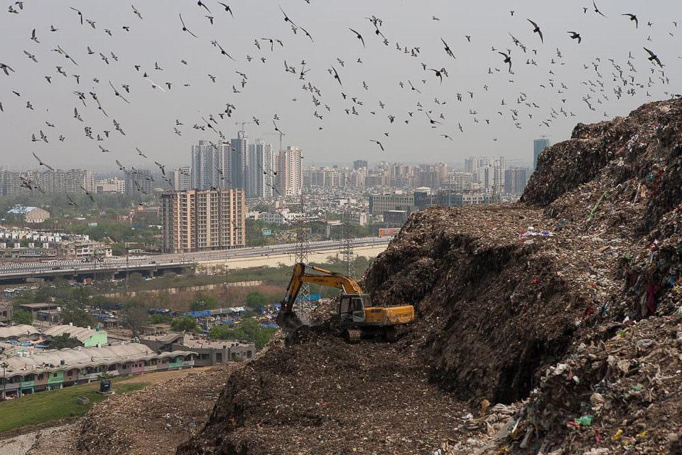 Ein Schaufelbagger verteilt Müll auf einer Müllhalde