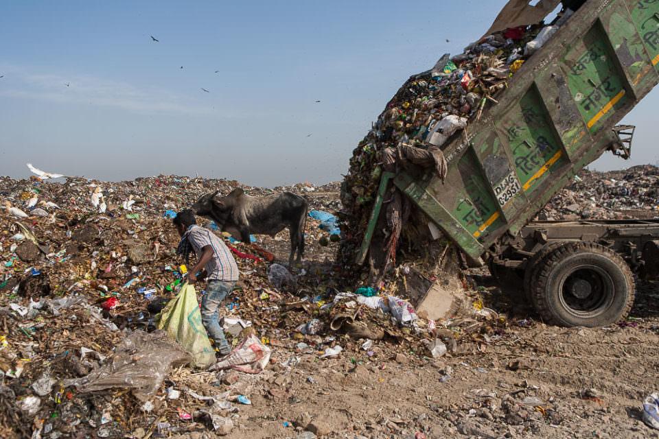 Ein Kipplaster liefert frischen Müll auf eine Müllhalde