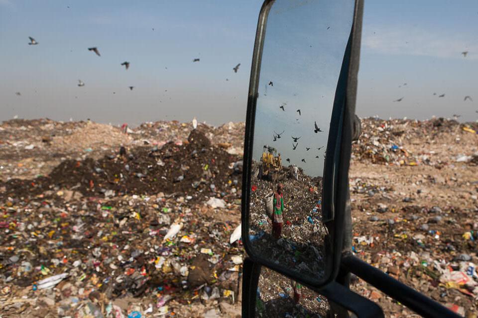 Eine Müllarbeiterin spiegelt sich im Außenspiegel eines Kipplasters