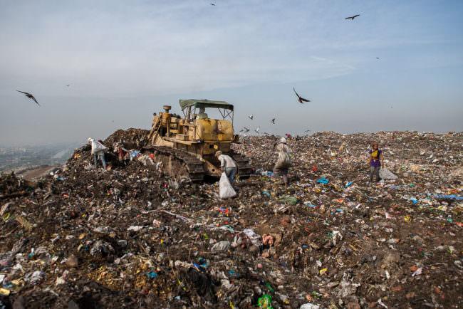 Während eine Planierraupe den frisch angelieferten Müll verteilt suchen Müllsammler*innen darin nach verwertbaren Teilen.