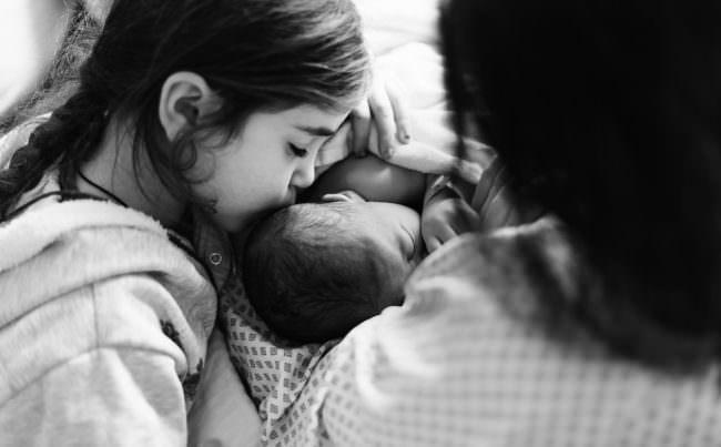 Kind küsst Neugeborenes