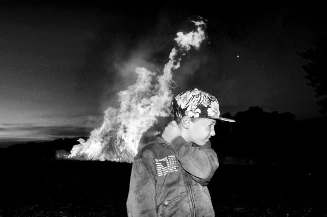 Ein Junge vor einem großen Feuer