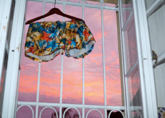 Bunte Badehose hängend im Fenstergitter