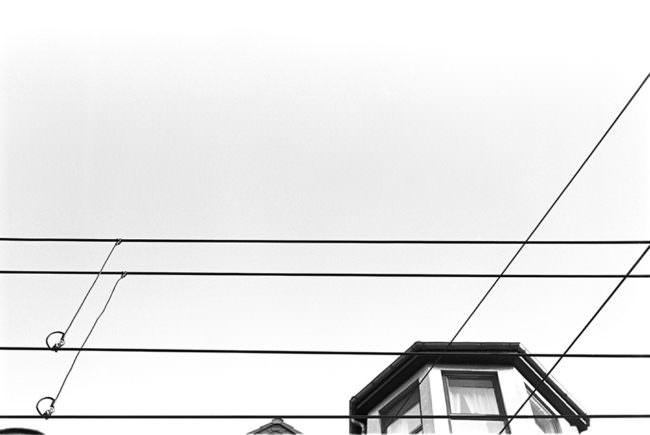 Hochleitungen im Himmel mit einer Häuserecke.