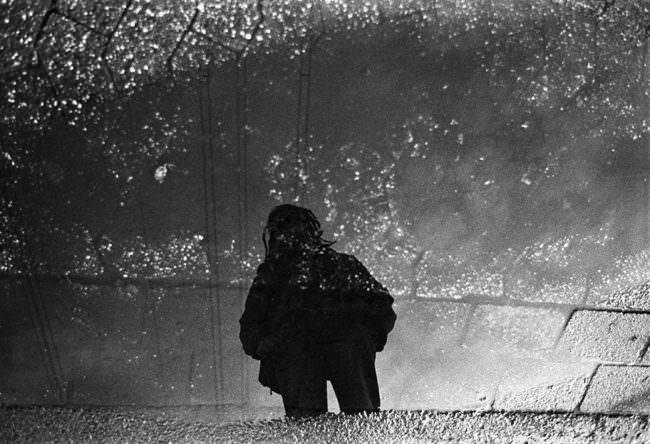 Spiegelung einer Person in einer Pfütze am Boden.