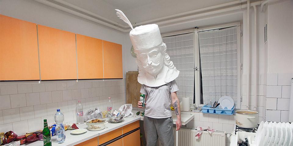 Person mit Pappmachée Kopf aufgesetzt in einer Küche.