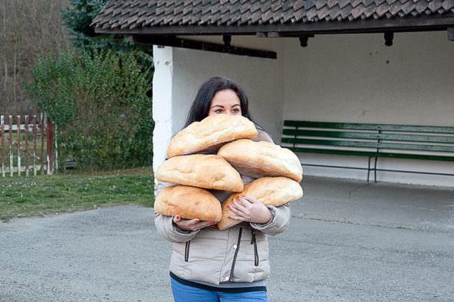 Frau hält viele Brotlaibe vor ihr Gesicht.