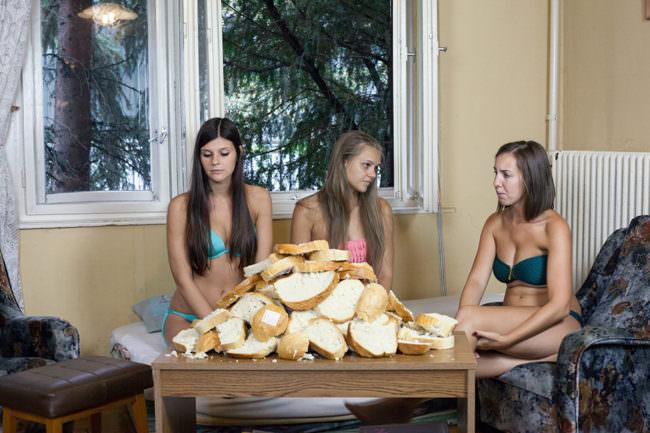 Drei junge Frauen in Bademode neben Tisch mit Brotlaiben.