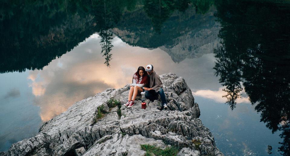 Pärchen auf einem Fels vor einem See