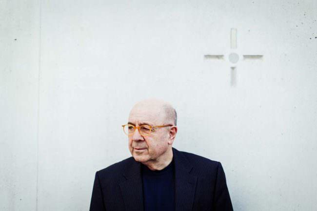 Portrait eines älteren Herren mit Brille vor einer Wand mit Kreuz.