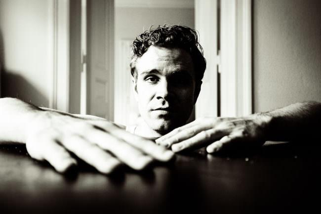 Portrait eines jungen Mannes mit Händen im Vordergrund.