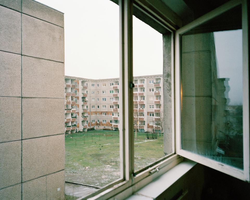 Ausblick aus einem Fenster auf eine Plattenbausiedlung.