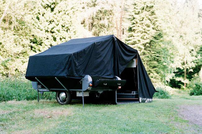 Campinganhänger mit schwarzem Zelt.