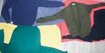 Verschiedene, bunte Kleidungsstücke ausgebreitet übereinander geschichtet