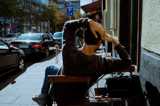 Ein Mann sitzt in der Sonne an einer Straße