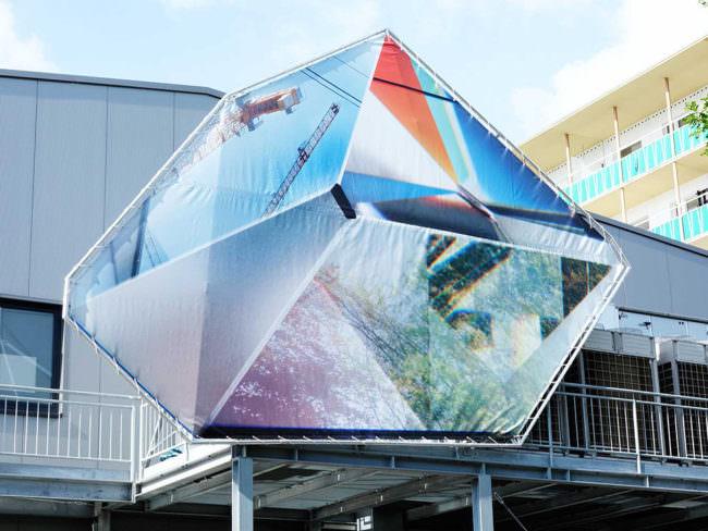 Prismenförmiges Banner an einer Hausfassade