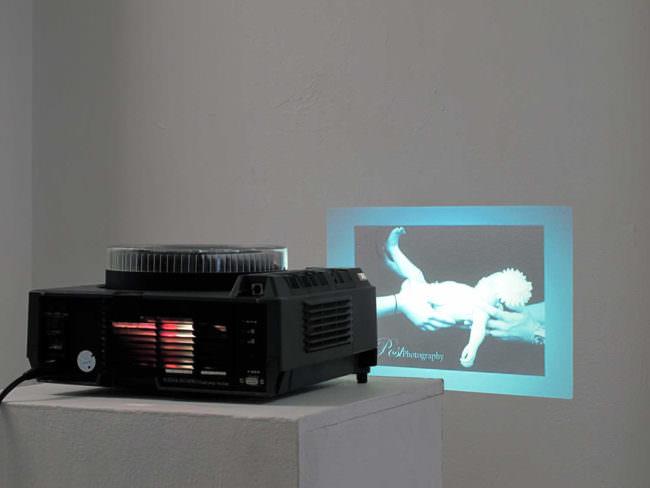 Diaprojektor und im Hintergrund Bild eines Säuglings