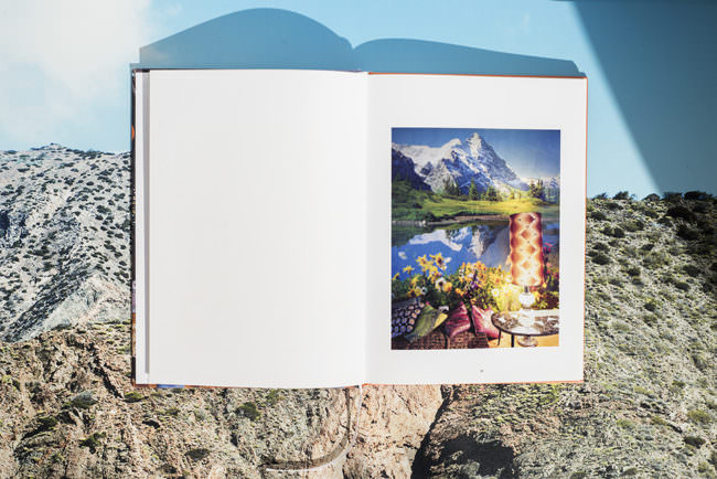 Ansicht eines offenen Buches mit Abbildung vor einer Berglandschaft.